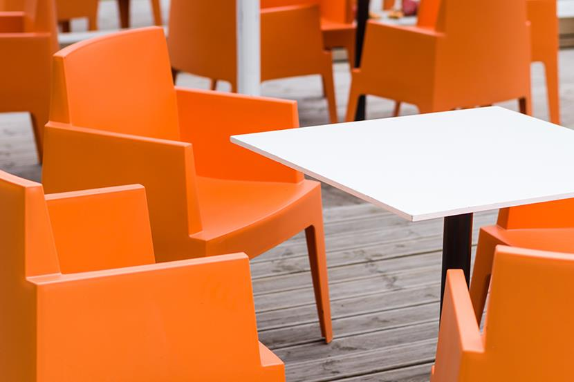 bright orange chairs white table sitting outside on a deck