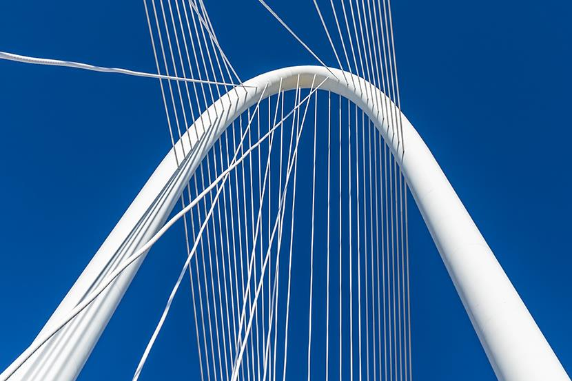 bright white suspension bridge against a deep blue sky