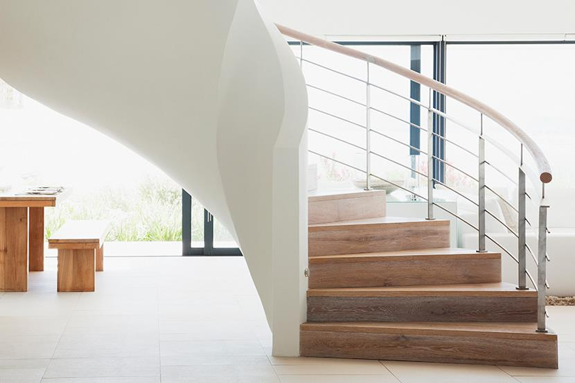 curving white standalone staircase in a bright white home