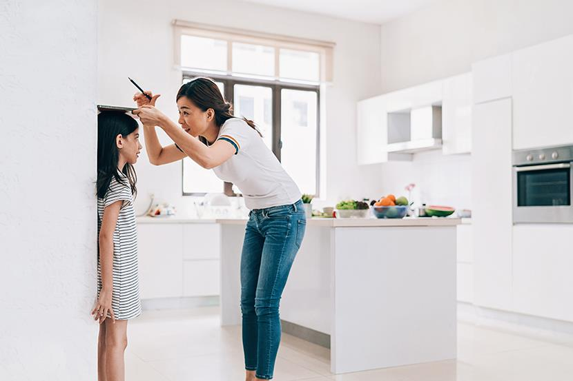 mother measuring the height of her daughter on the kitchen wall