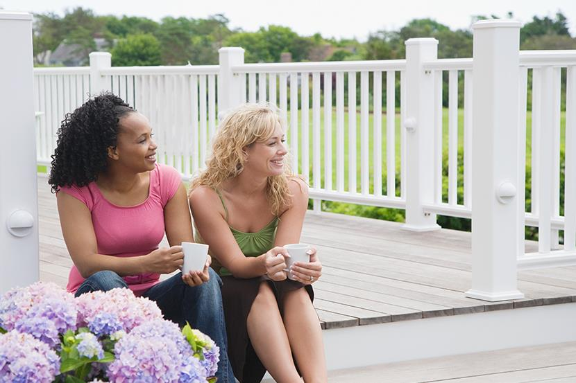 two women sitting on a porch holding coffee cups hydrangeas in the foreground