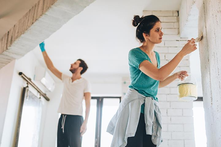 man and woman painting a room in a house